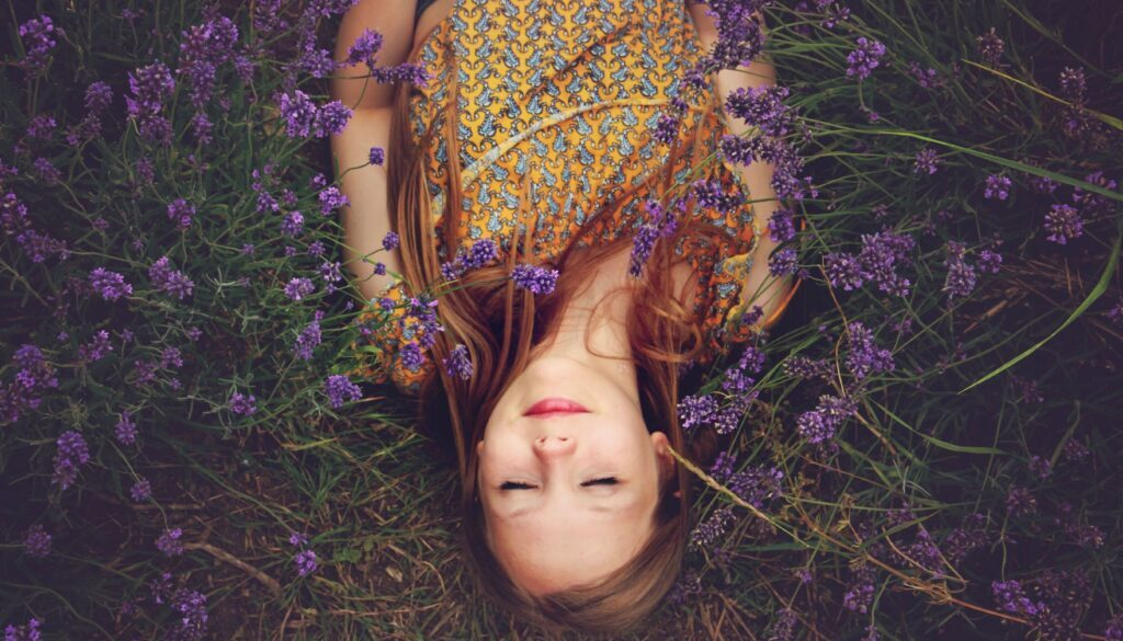woman lying in field at peace purple flowers