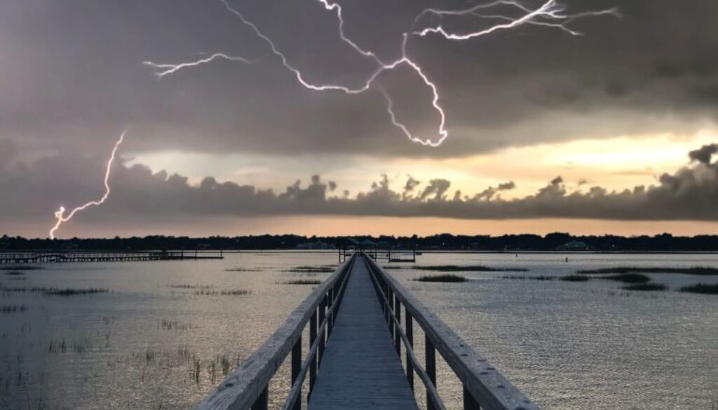 wooden dock on body of water with lightning