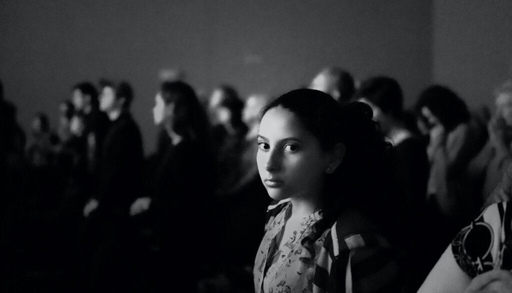 black and white picture of a young woman in a crowd pensively looking at the camera