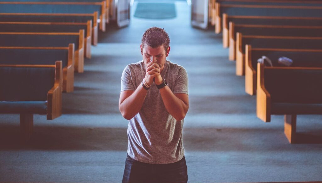 man in church on knees praying and begging God