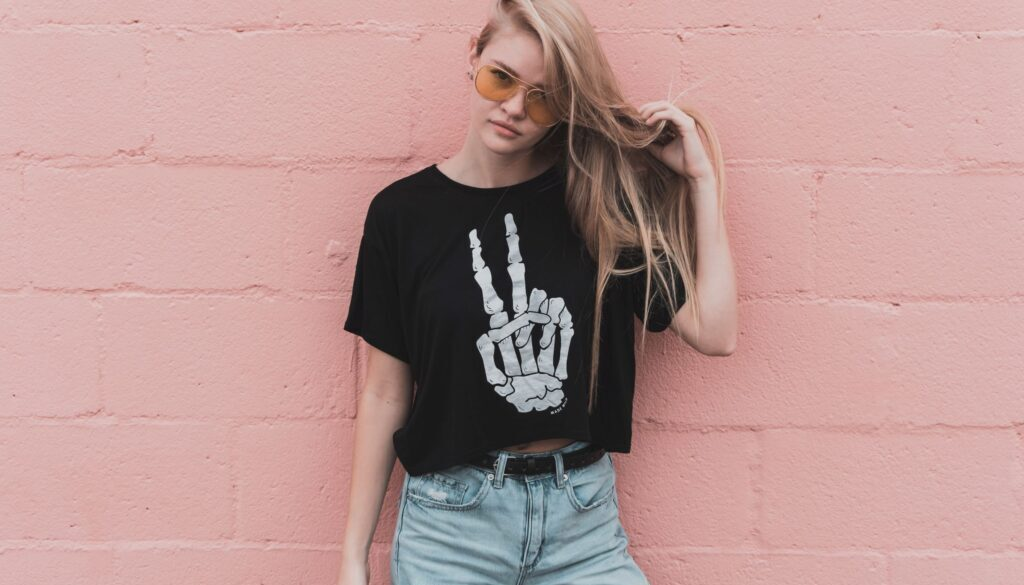 young woman standing against a wall wearing a skeleton tshirt and copping an attitude