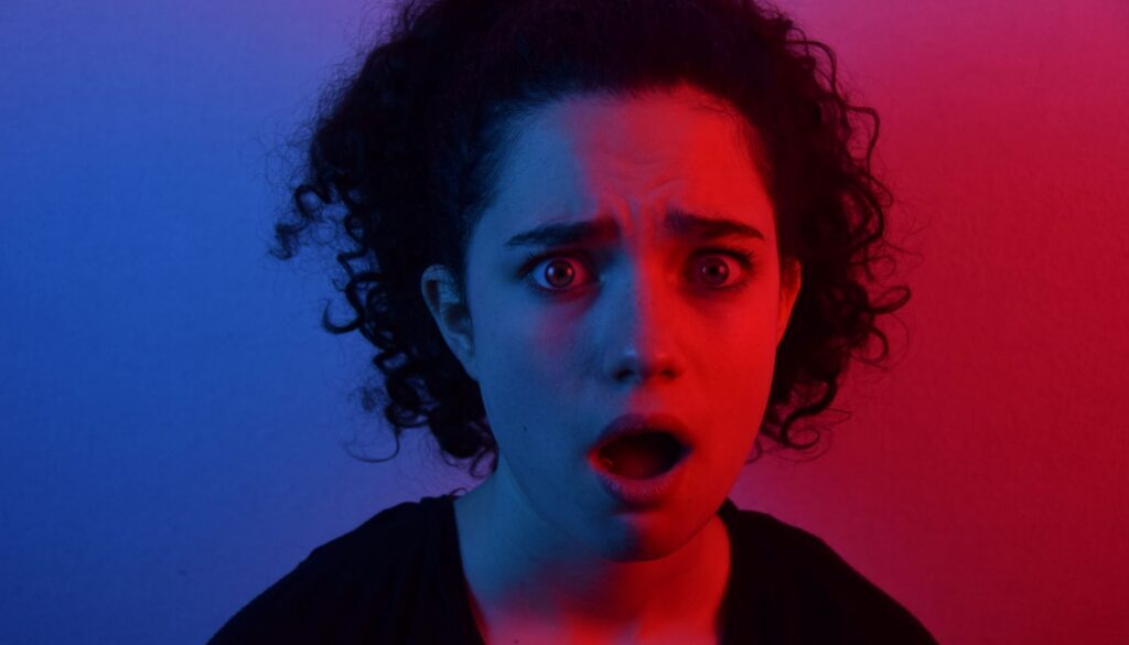 young woman with a surprised and pained look on her face against a multicolored background