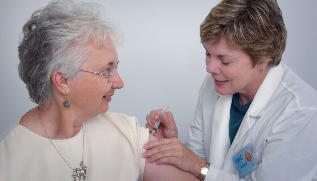 doctor giving a patient a shot or injection and both are smiling both are females and look healthy