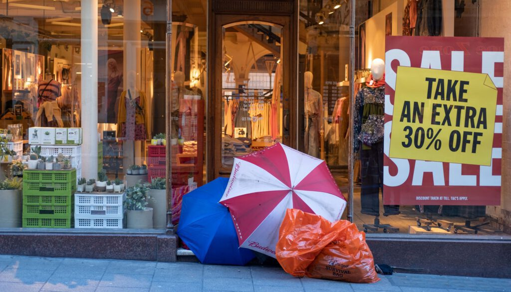 storefront sale with open umbrellas and shopping bags sale signs and sidewalk items on display