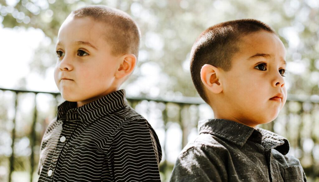 two serious looking little boys who look like brothers standing back to back outside with their backs turned to one another