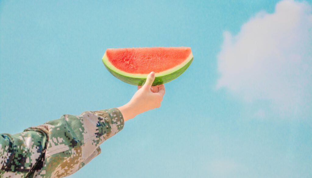 woman's arm and hand holding up a slice of watermelon against a fresh blue sky with white clouds