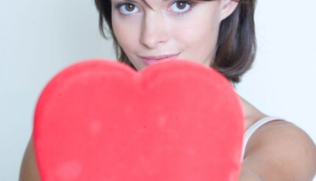 young woman holding a large red heart