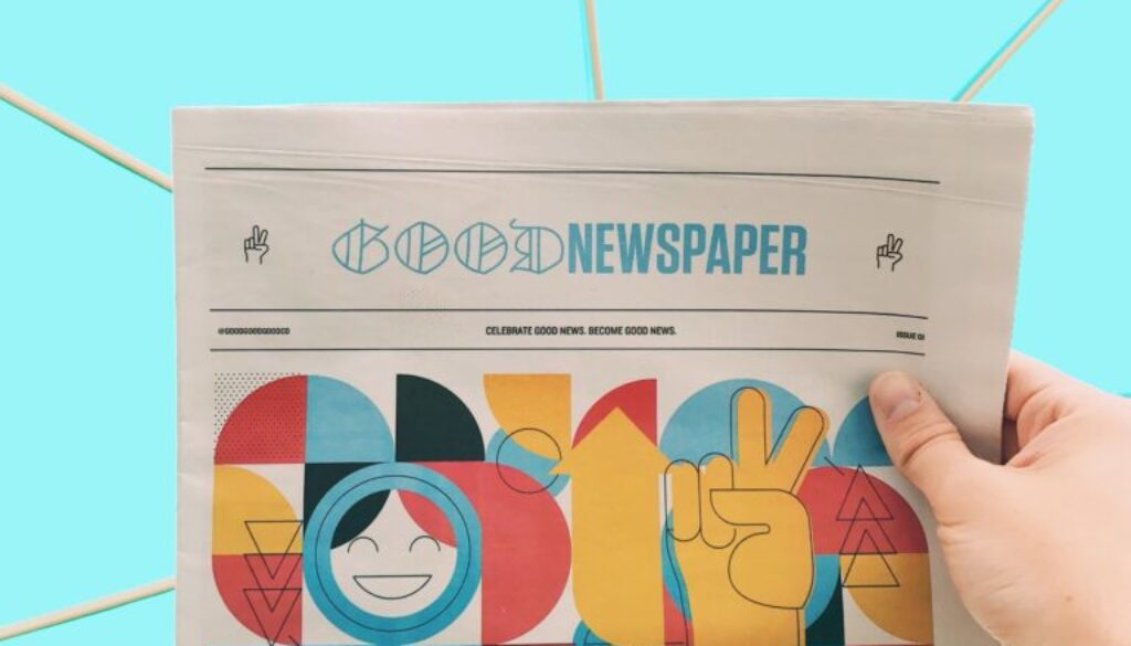 """picture of a hand holding up a colorful newspaper with the headline """"good newspaper"""" next to a bright happy background"""