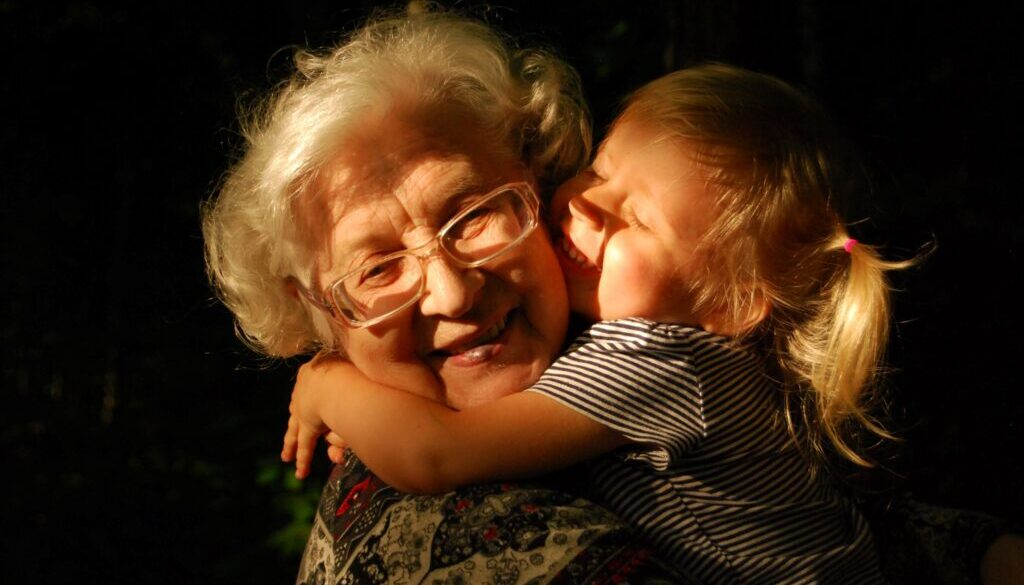 grandmother and little girl who are both happy and smiling in a ray of sunlight