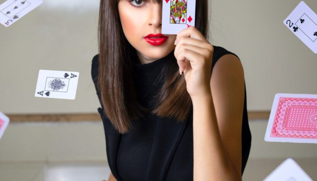 young woman holding the queen of hearts while sitting at a gambling table with cards flying all around