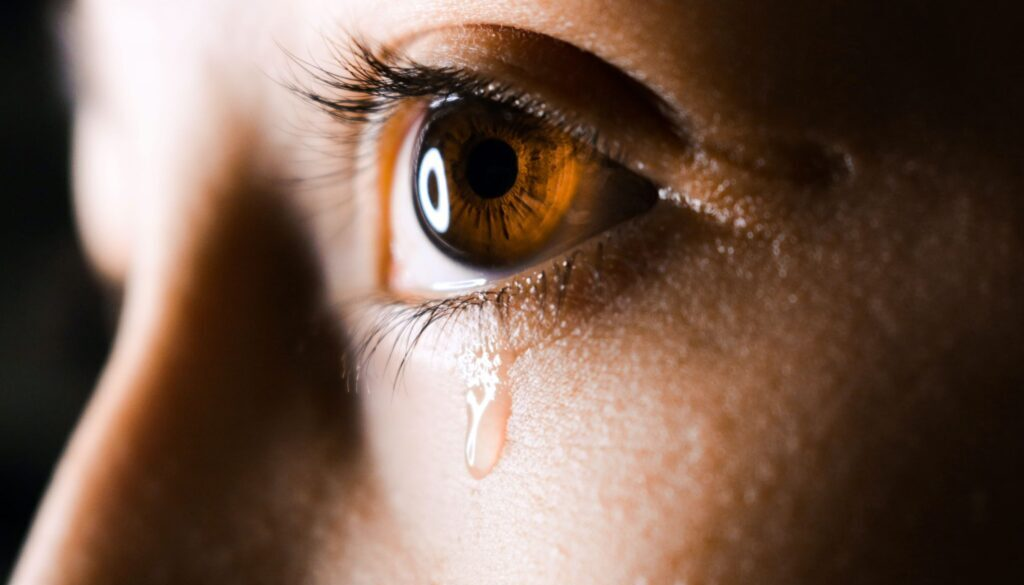 close up photo of a young woman with a tear in her eye