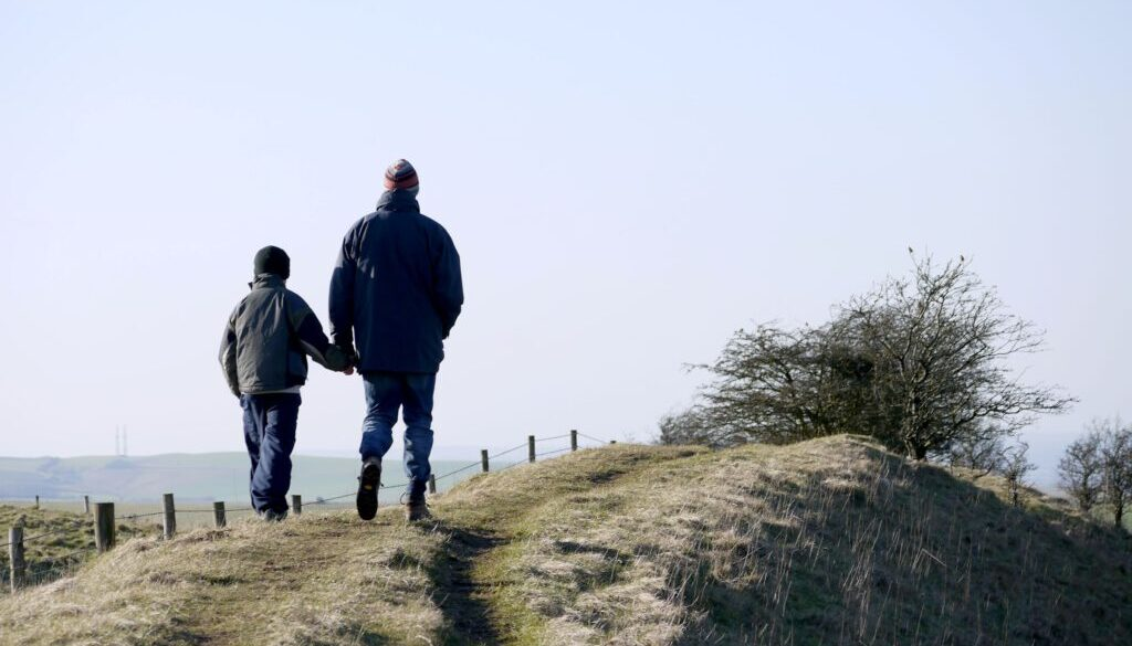 father holding his son's hand as they walk down a rural trail in a ranch like setting
