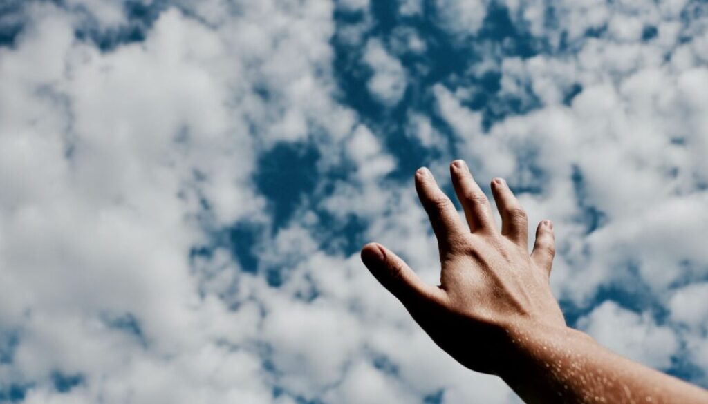 Man's hand reaching for the skies