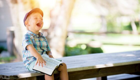little boy in cap sitting outside on a wooden bench laughing as he reads the Bible
