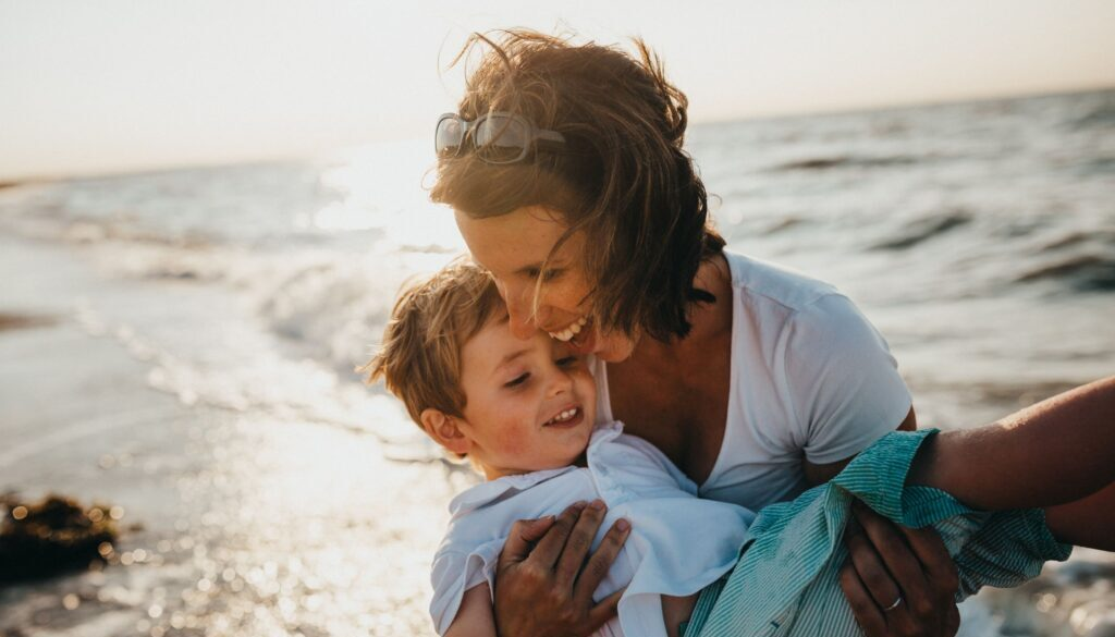 mother happily carrying her son outside on a beach by the ocean this is a joyful scene