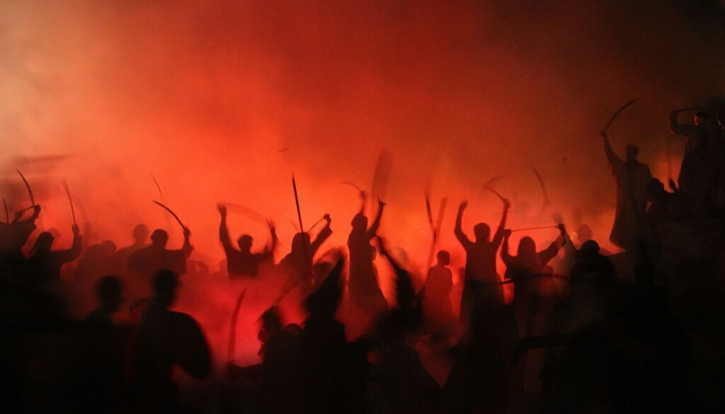 people at war with one another holding up swords and other weapons while silhouetted in front of a blood red sky