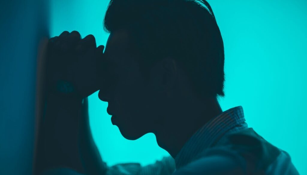silhouette of a young man against a blue background with hands his folded leaning against a wall praying