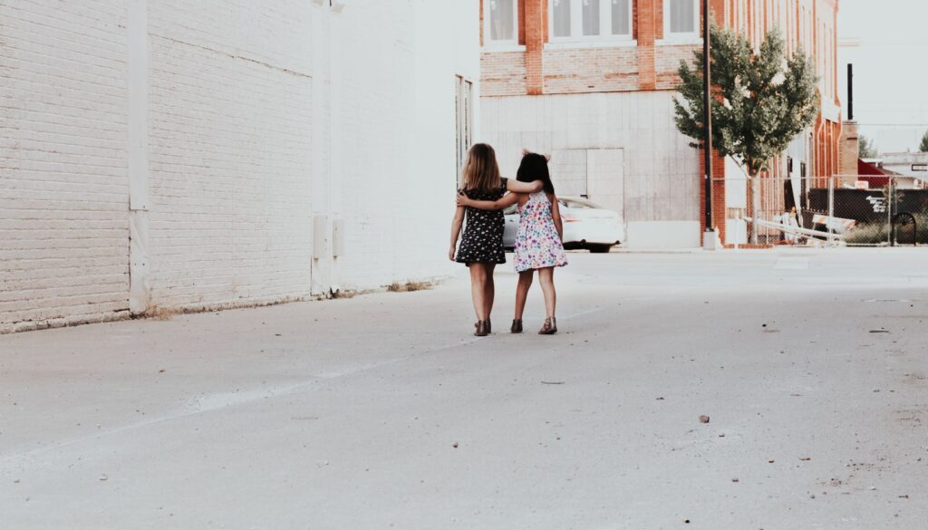 two little girls walking arm in arm down the alley of a big city