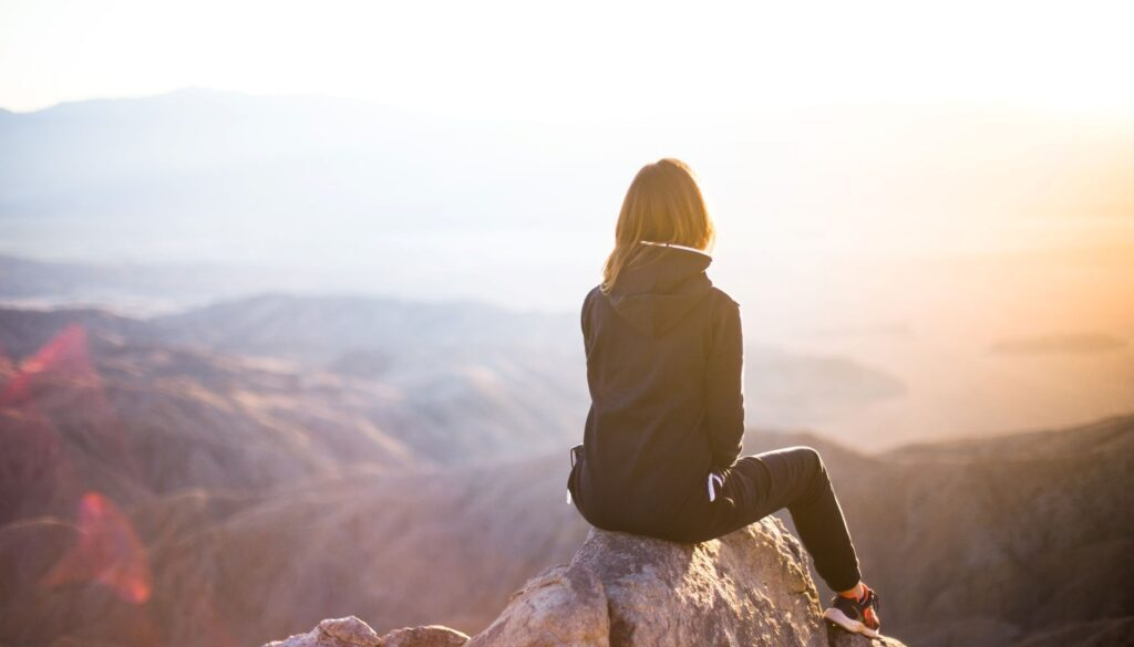 young woman sitting on the top of a mountain looking over the panorama of nature
