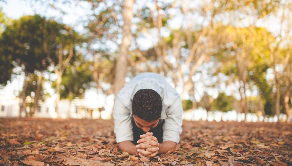 young man outside kneeling in prayer on a carpet of brown leaves in a wooded area