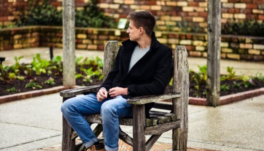 young man sitting outdoors who seems to be aimless and wondering