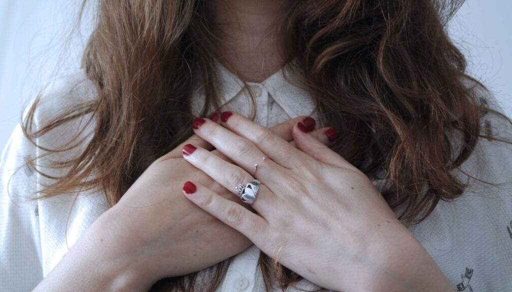 young woman holding her hands over her heart