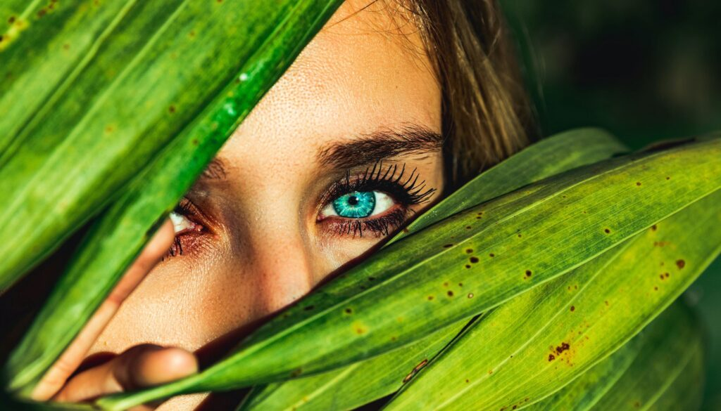 young woman with beautiful blue eyes hiding behind greenery and peeking out