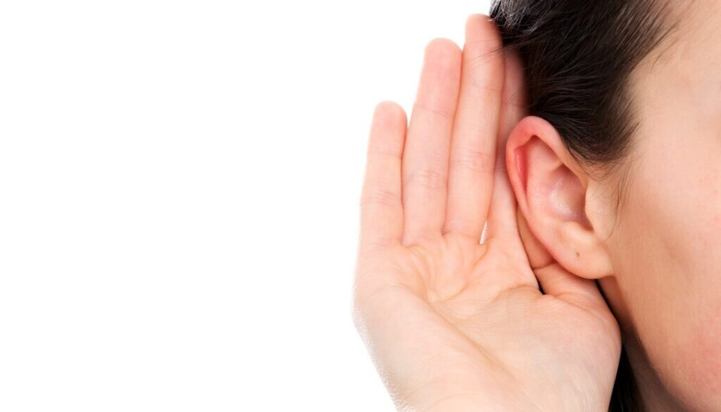 young woman cupping her hand behind her ear to hear better