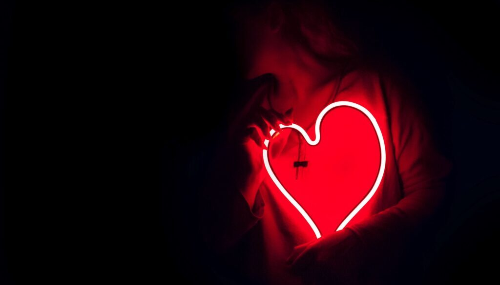 young woman holding a neon heart up to her chest