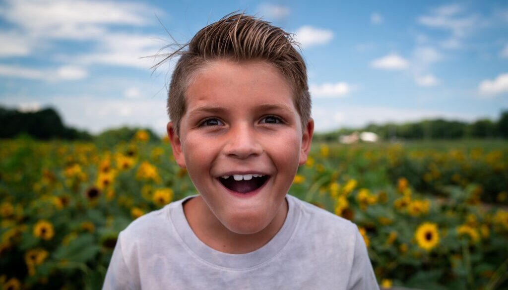 boy who is happy and smiling in a sunflower field