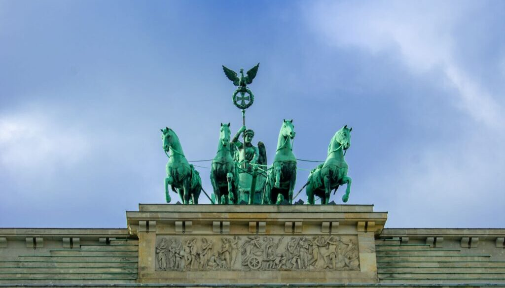 Brandenburg Gate with statues of quadriga backed by a clear blue sky