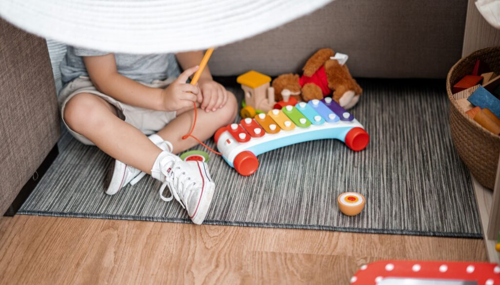 child sitting on the floor on a rug and playing with a toy xylophone