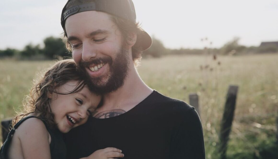 Man carrying his happy daughter outside on a sunny day