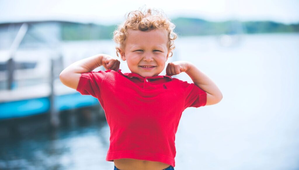 little boy flexing his muscles outside next to a dock