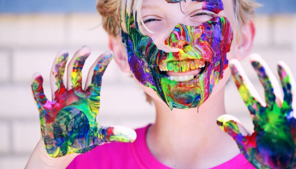 little boy smiling and wearing a magenta colored tshirt whose hands face and teeth are covered in multicolored paint