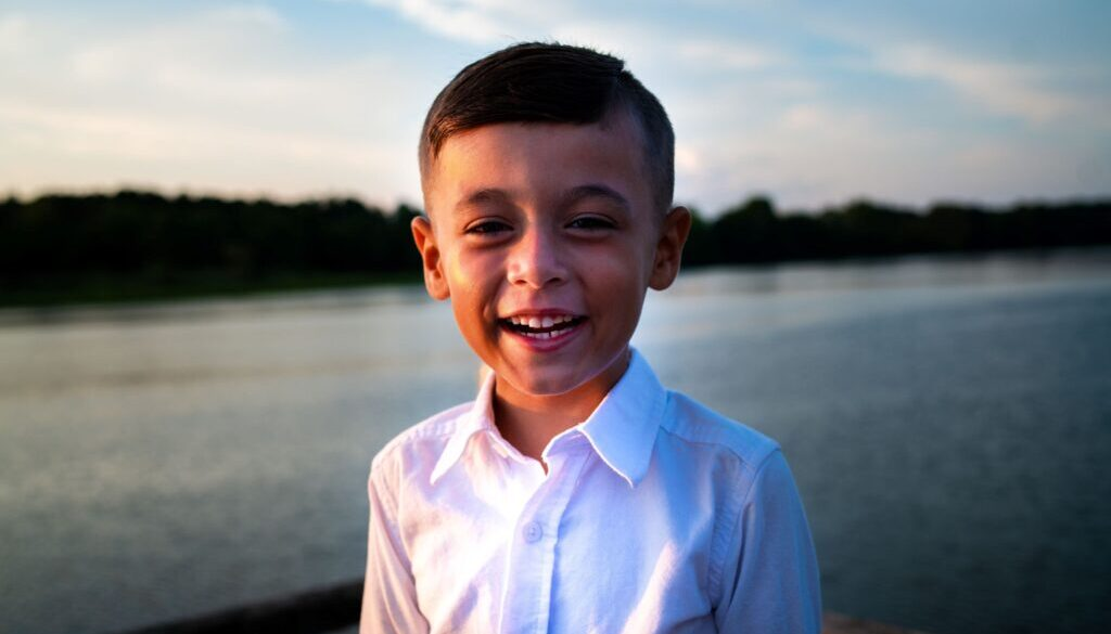 little boy in a white shirt smiling in an outdoor setting in front of a lake