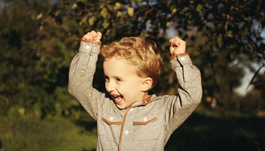 little boy standing in a grove of trees smiling with his hands raised enthusiastically