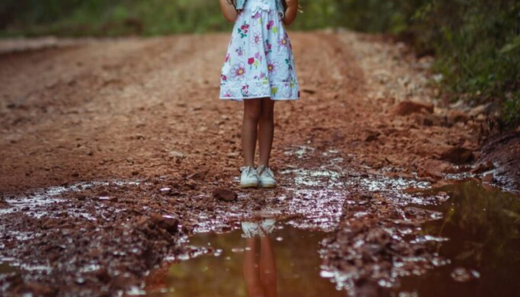 little girl in a summer dress and a floppy hat standing by a puddle on a rural dirt road
