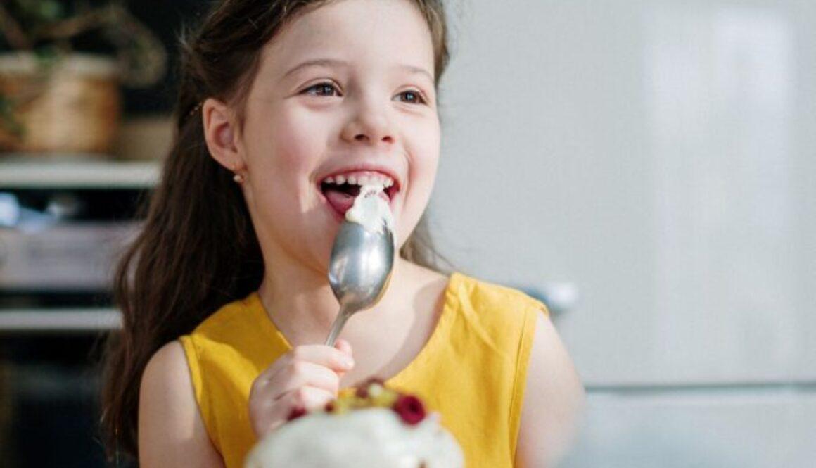 little girl sitting at a table lickingi icing off a spoon