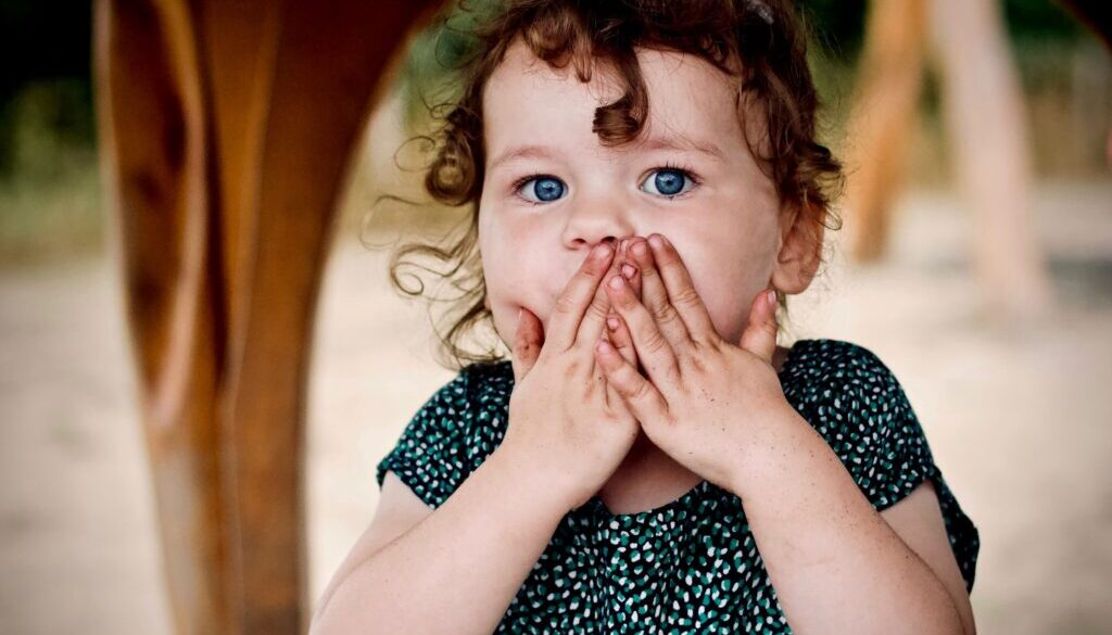 cute little girl with her hands over her mouth