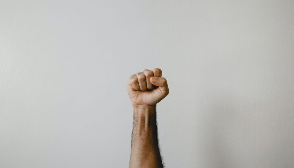 man's fist raised against a gray background