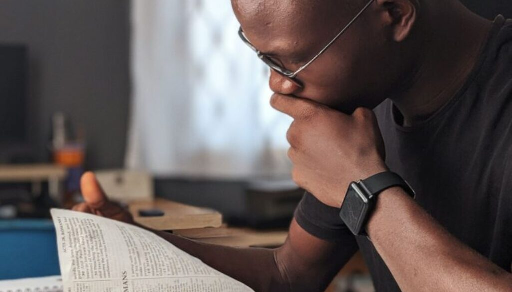 young man wearing glasses studying the Bible