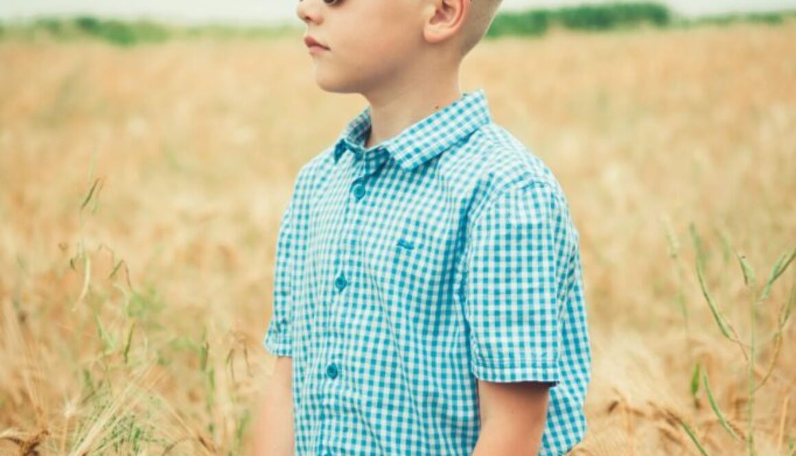 boy around early elementary age with blonde hair checked shirt and sunglasses standing in the middle of a wheat field