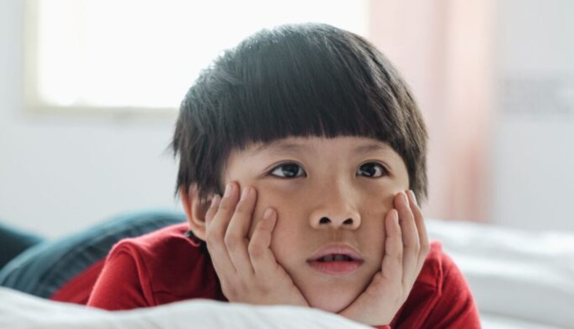 boy with bangs lying on a bed with his head propped up on his hands