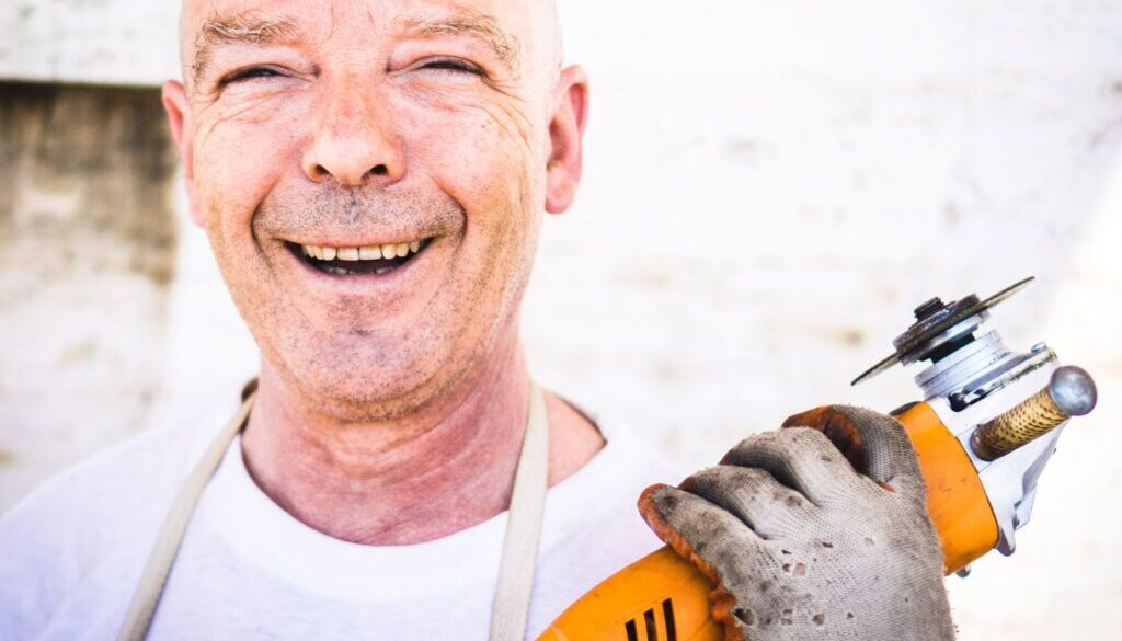 construction worker who is happy and smiling as he holds up a concrete cutting saw