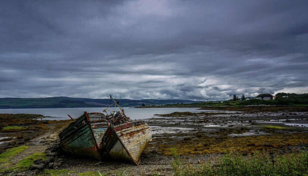 desolate landscape with wrecked hulls of two boats in the foreground