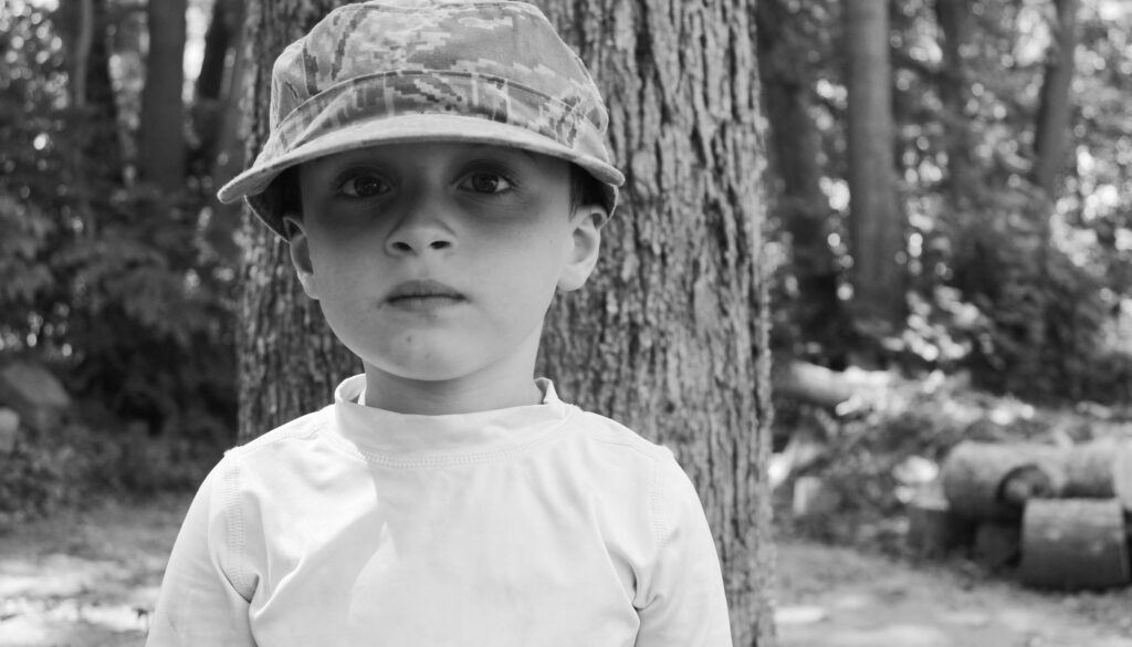 four year old boy in a hat standing outside in a forest this is a black and white photo