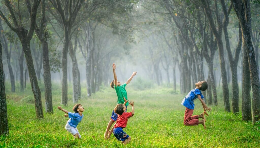 group of little boys frolicking in a green meadow framed by trees