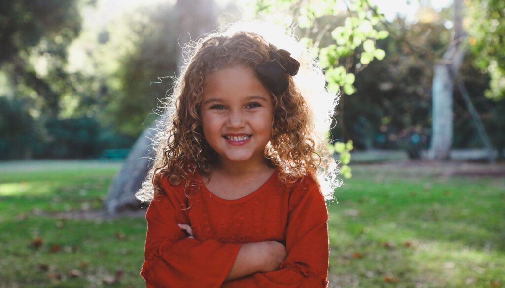 little girl smiling in a field with trees in the distance and backlit by the sun