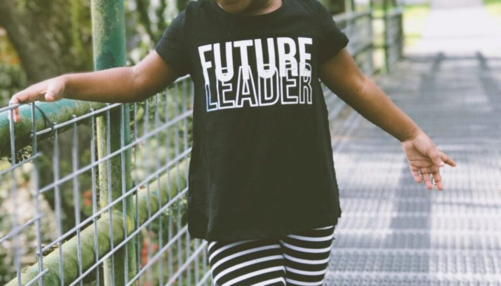 little girl standing outside on a bridge wearing a tshirt that reads future leader